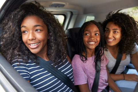 Three sisters look out the car window as they arrive at their parent's home.