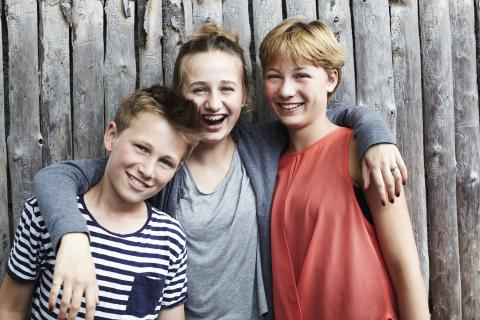 A girl puts her arms around her sister and brother as all three stand laughing as they pose for a picture