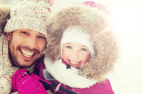 Father and daughter laughing outside during the winter, bundled up