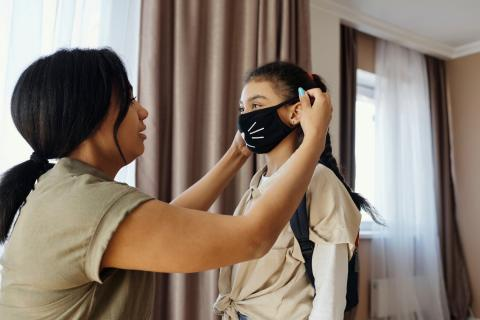 A mother helps her young daughter put on a face mask.