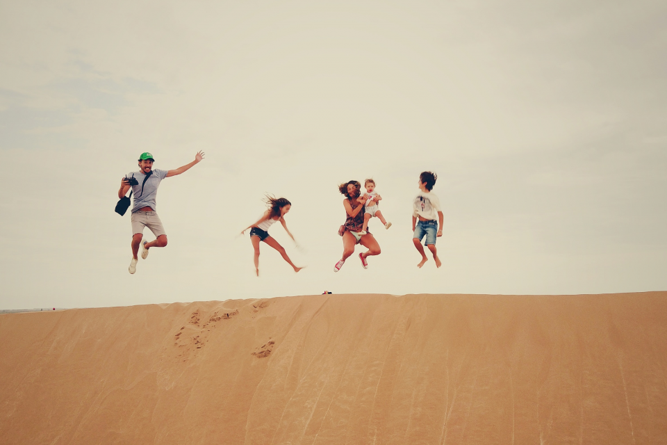 Family jumps in unison at the top of a sand dune