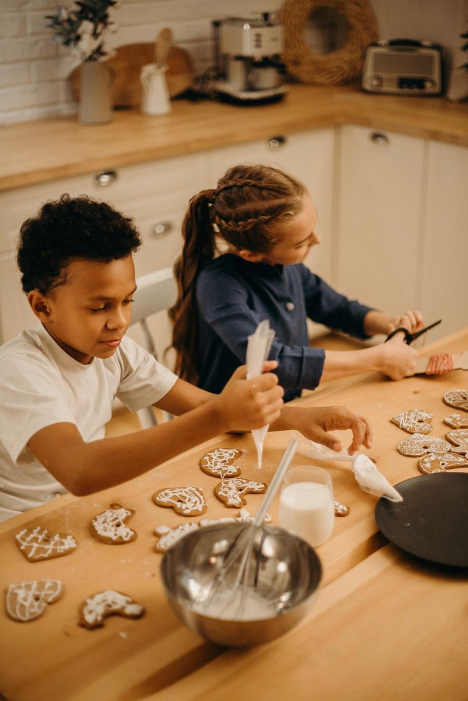 Two kids decorate cookies in the kitchen